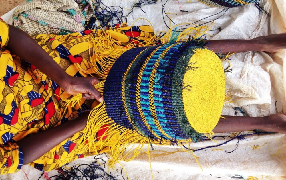 Artisan weaving Raffia hand dyed threads into a bag, at the A A K S workshop in Kumasi.